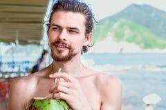 年轻可爱的人喝汁液绿色椰子和看在海湾和山的背景 免版税库存图片