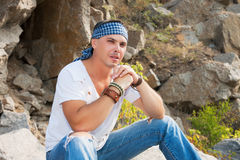 可爱的人坐在山的一个岩石 免版税图库摄影