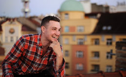 年轻可爱的人坐看起来的屋顶去和微笑 背景城市 库存照片