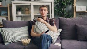 可爱的人学生哭泣在电视的哀伤的戏曲 年轻人坐舒适的沙发并且对负遥远 股票录像