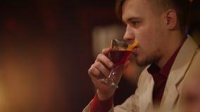 可爱的人是嗅到和喝红色利口酒在与软的内景照明的酒吧 影视素材