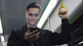 可爱的人画象耳机的拿着扶手栏杆,观看在智能手机的录影在公共交通工具 城市 股票视频