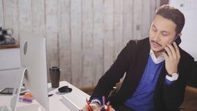 可爱的人谈论项目由电话在办公室 影视素材