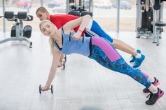 可爱的体育人民解决与在健身房的哑铃 免版税库存照片