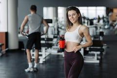 可爱的体育女孩微笑的和饮用水,当站立在与男孩训练的健身房在背景时 库存图片
