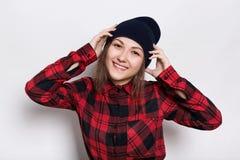 可爱的佩带黑盖帽和红色的行家年轻女性特写检查了握她的在头的衬衣手有魅力 免版税库存图片