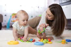 可爱的使用在托儿所的婴孩和少妇 获得愉快的家庭与五颜六色的玩具的乐趣在家 免版税图库摄影