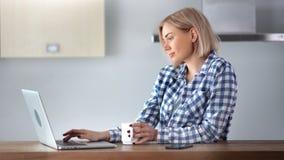 可爱的使用膝上型计算机工作和饮用的咖啡的自由职业者妇女键入的文本在家 影视素材