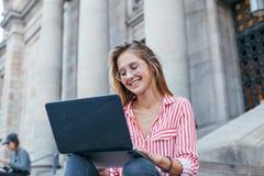 可爱的俏丽的学生坐有膝上型计算机的台阶 免版税库存照片