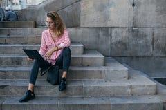 可爱的俏丽的学生坐有膝上型计算机的台阶 图库摄影