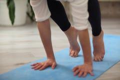年轻可爱的信奉瑜伽者女子实践的瑜伽,设法做起重机摆在,特写镜头射击了用手和腿 免版税图库摄影