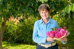 可爱的前辈在她的有桃红色罗斯花束的庭院里 免版税库存图片