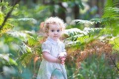 可爱的卷曲女婴在晴朗的公园 库存图片