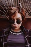 可爱的厚颜无耻的妇女画象有短的红色头发的在太阳镜 免版税库存图片
