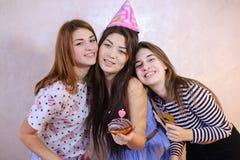 可爱的友好的女孩庆祝生日他们的女性朋友 免版税库存照片