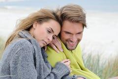 可爱的可爱的妇女和人在放松的海滩的沙丘坐-秋天,海滩,海 免版税图库摄影