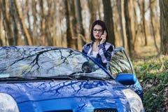 可爱的司机女孩看在门户开放主义汽车和谈话外面 免版税库存照片
