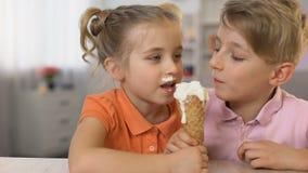 可爱的吃冰淇凌的兄弟和姐妹一起坐家庭桌,食物 影视素材