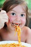 可爱的吃的女孩少许意大利面食 免版税库存图片