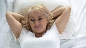 可爱的唤醒妇女放松在床上的早晨,健康和秀丽,休闲 免版税库存照片