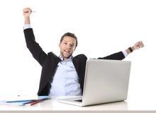 年轻可爱的商人愉快和忙碌在坐在计算机书桌的事务满足了庆祝 免版税库存图片