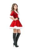 可爱的圣诞老人女孩侧视图摆在用在臀部的手的圣诞节礼服的 免版税库存图片