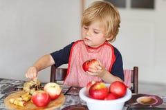 可爱的在家庭' s kitc的小男孩帮助的和烘烤的苹果饼 免版税库存照片