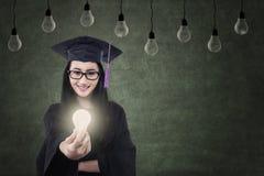 可爱的在灯下的女性毕业生给的被点燃的电灯泡 免版税库存照片