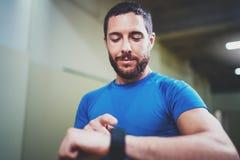 年轻可爱的在电子聪明的手表应用的运动员跟踪的被烧的卡路里在好室内锻炼以后 免版税库存图片