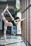 年轻可爱的在窗口附近的女子实践的瑜伽 免版税图库摄影