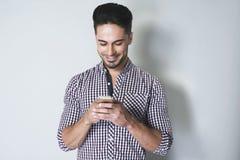 可爱的在他的手机的人键入的消息 免版税库存图片