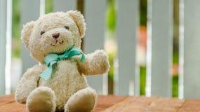 可爱的地毯熊玩偶坐木桌 免版税库存图片