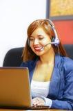 年轻可爱的坐由书桌的妇女佩带的办公室衣裳和耳机看屏幕,运转与 免版税库存图片