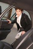 可爱的坚定的女商人旅客进入出租车 库存照片