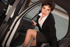 可爱的坚定的女商人旅客进入出租车 图库摄影