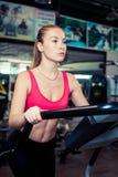 可爱的坚强的妇女在健身中心的做心脏训练计划 免版税库存图片