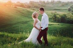 可爱的夫妇、摆在领域的新娘和新郎在日落,生活方式期间 免版税库存照片