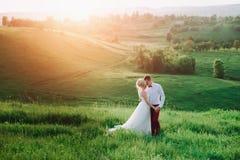 可爱的夫妇、摆在领域的新娘和新郎在日落,生活方式期间 库存图片