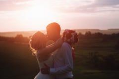 可爱的夫妇、摆在领域的新娘和新郎在日落,生活方式期间 免版税图库摄影