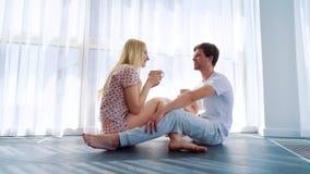 可爱的夫妇全景射击坐地板和饮用的早晨咖啡 股票录像