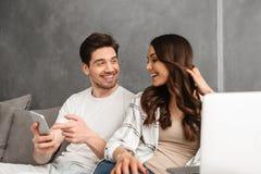 可爱的夫妇在家休息在客厅的男人和妇女30s 库存照片