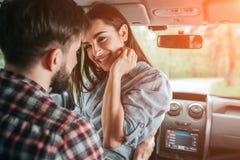 可爱的夫妇在汽车单独坐 女孩是坐面对面与她的男朋友 她保留她的手接近 库存图片