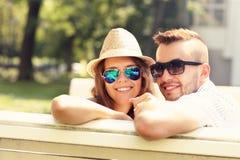 可爱的夫妇坐长凳 免版税库存照片