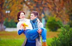 可爱的夫妇获得乐趣在秋天公园 免版税库存照片