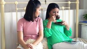 可爱的女儿给她的母亲带来热的咖啡在卧室 库存照片