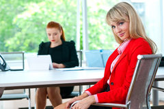 可爱的女商人在有同事的办公室在背景中 免版税库存照片