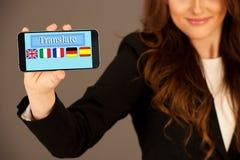 可爱的女商人拿着一种片剂或智能手机与翻译应用 免版税库存照片
