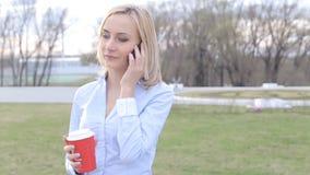 可爱的女商人通勤者谈话在走在城市的电话 股票录像