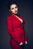 可爱的女商人 一个性感的年轻企业夫人的画象一套红色衣服的在黑暗的背景 免版税图库摄影