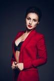可爱的女商人 一个性感的年轻企业夫人的画象一套红色衣服的在黑暗的背景 免版税库存照片